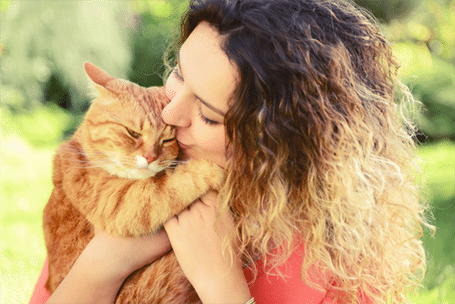 Woman hugging cat: Pet Dental Care Services in Dallas